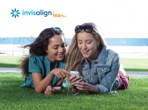 Two girls laying on grass with straight teeth wearing Invisalign