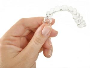 Hand holding an Invisalign retainer